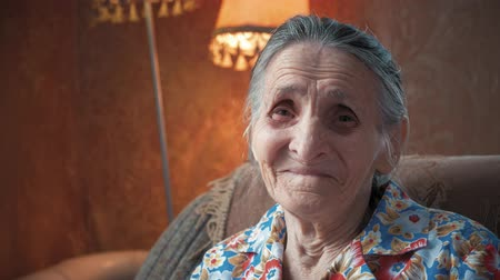 Portrait of an elderly woman 80-90 years old at home. Old odd lady with wrinkled skin face looking at camera. Detailed aged face skin. Great grandmother face expression. Senior granny female. Стоковые видеозаписи