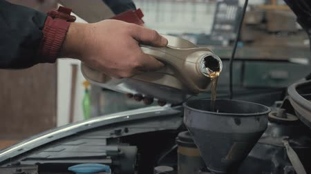 Car maintenance servicing mechanic pouring new oil lubricant into the car engine. Pouring fresh new clean synthetic oil into car engine. Change engine oil of your car. Stock Footage