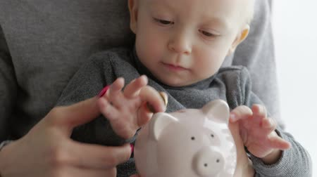 piggy bank : Mother and little son putting coins into piggy bank for the future savings.