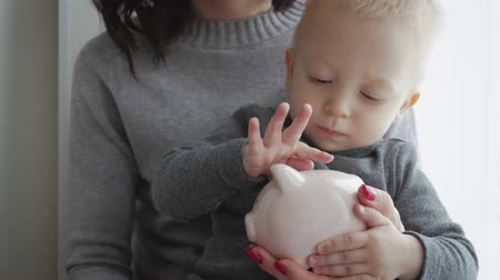Mother and little son putting coins into piggy bank for the future savings.
