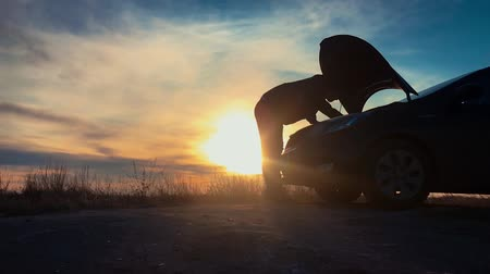 Silhouette man is checking engine bay of the broken down car while sunset. Стоковые видеозаписи