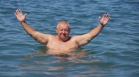 Peaceful carefree older man with outstretched arms. Man splashing water during summer holidays. Стоковые видеозаписи