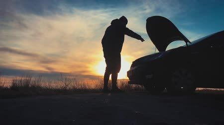 blut : Silhouette man is checking engine bay of the broken down car while sunset. Stockvideo