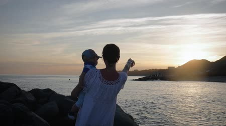 Young mother holding her son in her arms by the sea.