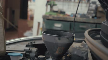 sentetik : Car maintenance servicing mechanic pouring new oil lubricant into the car engine. Pouring fresh new clean synthetic oil into car engine. Change engine oil of your car. Stok Video
