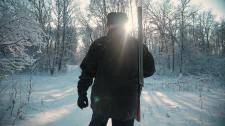 escopeta : Hunter walking in the snowy winter forest. Winter hobby, sun, hunting concept. Archivo de Video