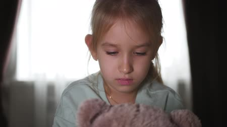 hatred : Portrait of a sad teenage girl and teddy bear lying in bed.