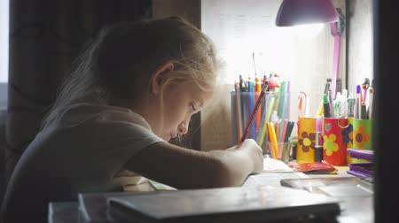 alfabetização : Young girl makes its homework at on the table under the light of a lamp. Creative hobby of little princess. lifestyle of talented people.