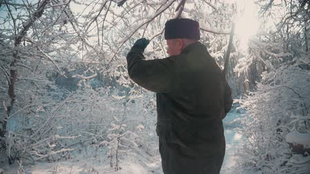 jachtgeweer : Hunter walking in the snowy winter forest. Winter hobby, sun, hunting concept. Stockvideo