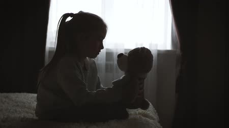 hatred : Depressed little girl hugging teddy bear.