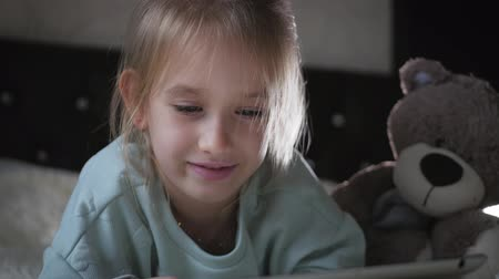 věčnost : Cute little girl sitting on bed together with teddy bear playing games on tablet. Dostupné videozáznamy