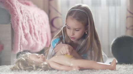 кукла : Beautiful little girl playing doctors with doll at home.