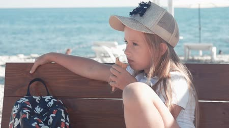 vacations cones : Teenage girl on summer holidays, talking sitting on seaside bench with ice cream. Child eating ice cream on beach.