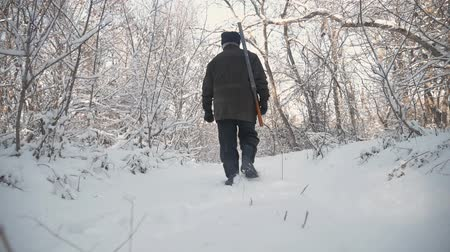 outdoor hobby : Hunter walking in the snowy winter forest. Winter hobby, sun, hunting concept. Stock Footage