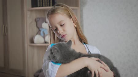 kittens playing : Child girl playing doctor with cat at home. Girl playing veterinarian with home pet.