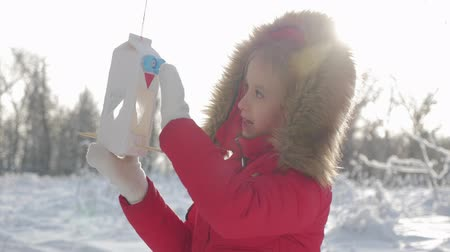 besleyici : Pretty cute girl at winter park with bird feeder. Bird feeder on tree, winter vacation and holidays concept, children outdoor activities.