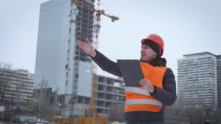 vágólapra : Business, building, paperwork and people concept - happy builder in hardhat with clipboard at construction site. Engineer builders with blueprint at construction site.