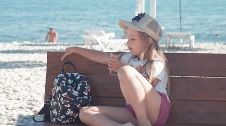конусы : Teenage girl on summer holidays, talking sitting on seaside bench with ice cream. Child eating ice cream on beach.