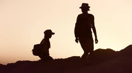 tourist silhouette : Silhouettes of mother and child tourists hiking at sunset. Mom and daughter on summer vacation carrying backpacks. Little girl following her mom on cliff edge. The concept of traveling with children. Stock Footage