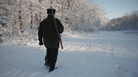 ohař : Hunter walking in the snowy winter forest. Winter hobby, sun, hunting concept. Dostupné videozáznamy