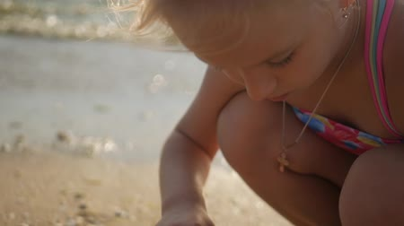 coletando : Happy little girl enjoying summer vacation collecting seashells. Seashell in girl hands close up.