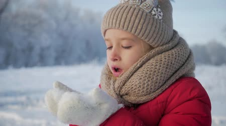başörtüsü : Happy young girl have fun and enjoy fresh snow at beautiful winter day. Girl in warm gloves blowing snow. Outdoors. Flying Snowflakes.