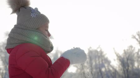 hófúvás : Happy young girl have fun and enjoy fresh snow at beautiful winter day. Girl in warm gloves blowing snow. Outdoors. Flying Snowflakes.