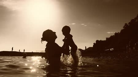 maternidade : Young mother holding her son in her arms by the sea.