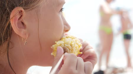 голодный : A little blond girl is eating corn on the beach. Стоковые видеозаписи