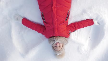 snow angel : Happy girl lying on a snow and shows angel. A pretty girl in a coat lies on the snow, spreading her arms.