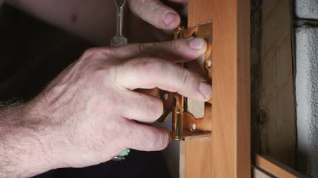 винты : Close-up carpenter process of wood door hinge installation. Door hinge installation.