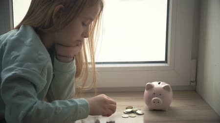 prase : Happy girl save money in piggy bank in her home. Child inserting a coin into a piggy bank, indoor financial concept. Kid saving money for future concept. Dostupné videozáznamy