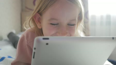 tabletler : Cute little girl holding digital tablet and smiling while lying in bed. Beautiful girl playing on tablet pc. Education, school, technology and internet concept.