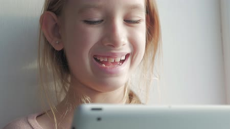 sorrisos : Cute little girl holding digital tablet and smiling while lying in bed. Beautiful girl playing on tablet pc. Education, school, technology and internet concept.