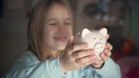 cerdo bebe : Happy girl save money in piggy bank in her home. Child inserting a coin into a piggy bank, indoor financial concept. Kid saving money for future concept. Archivo de Video