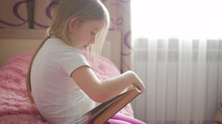 pizsama : Girl child lay bed read book. Girl kid long hair cute pajamas relax and read fairytale book. Pleasant time in cozy bedroom.