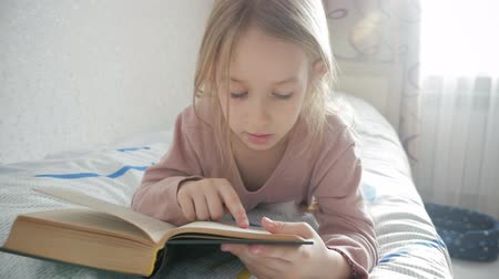 stories : Girl child lay bed read book. Girl kid long hair cute pajamas relax and read fairytale book. Pleasant time in cozy bedroom.