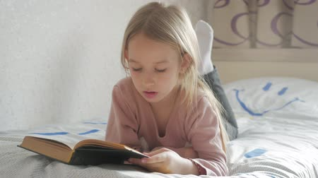 敷設 : Girl child lay bed read book. Girl kid long hair cute pajamas relax and read fairytale book. Pleasant time in cozy bedroom.