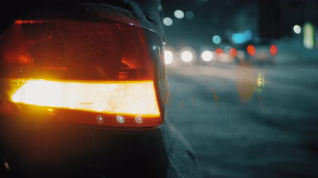 vészhelyzet : Emergency car warning light on the background of moving cars on a night road city. Winter road traffic cars breakdown outdoors.