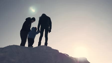 cold sunset : Happy family at sunset. Father, mother and little son are having fun and playing on snowy winter walk in nature.