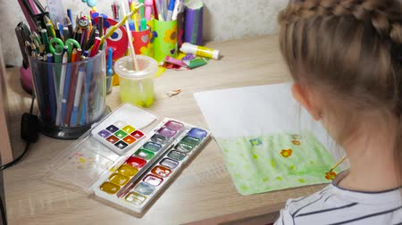 przedszkole : Teenage girl at home is engaged in creativity, draws watercolor at a table in room. Child drawing top view. Artwork workplace with creative accessories.