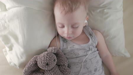 comfortable : Sweet baby boy in headphones sleeping with teddy bear. Stock Footage