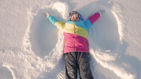 neşeli : Happy girl lying on a snow and shows angel. A pretty girl in a coat lies on the snow, spreading her arms.