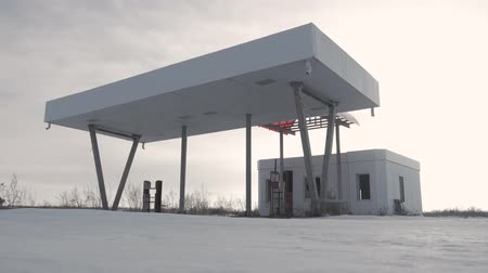 ileri : View of derelict gas station next to the road in a winter. Abandoned Petrol Station with No Fuel signs covering the pumps, victim of the economic crisis. The historic route 66. Stok Video