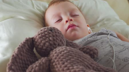 ártatlanság : Sweet baby boy in headphones sleeping with teddy bear. Stock mozgókép