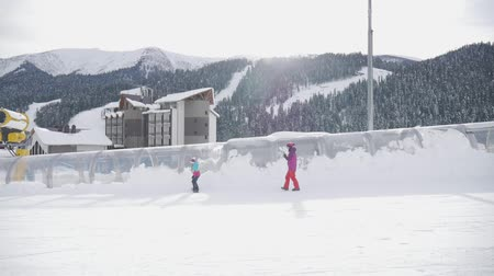 hegyoldalban : Mother helps her daughter to properly ride on snowboard on ski slope. Winter vacation concept.