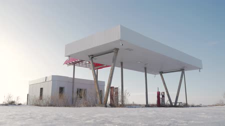 filling station : View of derelict gas station next to the road in a winter. Abandoned Petrol Station with No Fuel signs covering the pumps, victim of the economic crisis. The historic route 66. Stock Footage