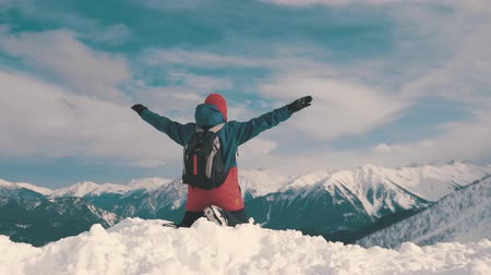 kabarık : Man with backpack standing on snowy mountain top in winner pose with raised hands enjoying view and achievement on bright sunny winter day. Concept adventure, outdoors activities, healthy lifestyle.