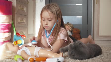 nevinný : Beautiful little girl playing doctors with doll at home.