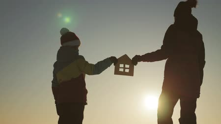 jak : Silhouette happy mother and daughter with dream house. Paper house as a symbol. The concept of family happiness.